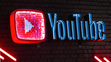 YouTube name and logo in bright, neon lights
