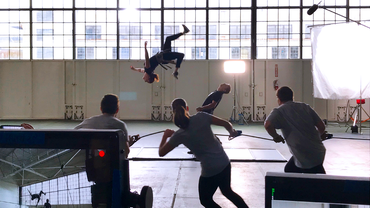 Video production crew from VMG Studios filming a stunt school of a woman doing a backflip in a warehouse setting